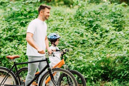 Photo pour Vue latérale du fils et du père debout avec des vélos près de la forêt et impatient - image libre de droit