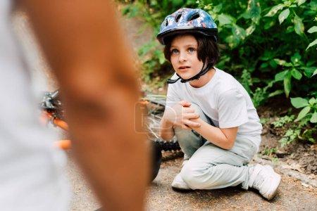Photo pour Foyer sélectif du garçon est tombé du vélo et regardant le père tandis que le père restant près du fils - image libre de droit