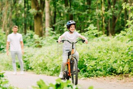 Selektiver Fokus des glücklichen Jungen, der Fahrrad fährt, und des Vaters, der steht und Sohn ansieht