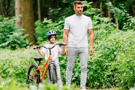 full length view of father and son standing on road near forest and looking forward while son holding bicycle