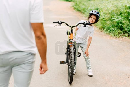 Photo for Selective focus of boy touching knee while father standing near son - Royalty Free Image