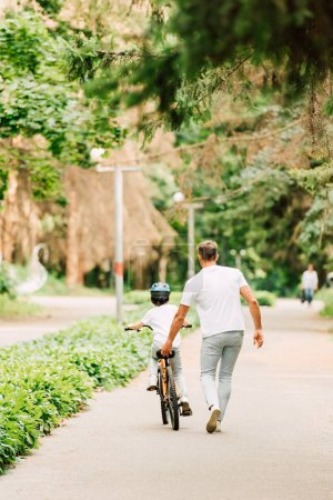 Photo for Full length view of father helping son to ride by holding sit of bicycle - Royalty Free Image