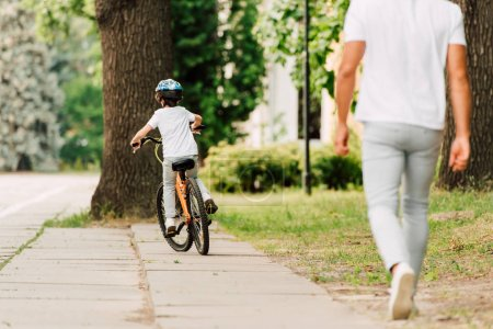Photo for Back view of kid riding bicycle while father walking after son - Royalty Free Image
