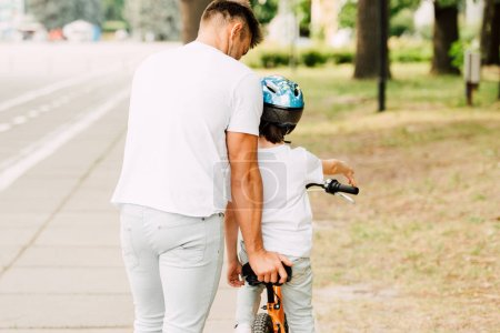Photo for Back view of father helping son to ride on bicycle while kid sitting on bike - Royalty Free Image