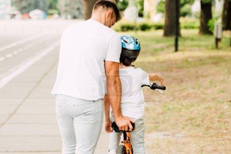 Photo pour Vue arrière du père aidant son fils à monter à vélo tandis que l'enfant assis sur le vélo - image libre de droit