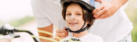 Photo for Panoramic shot of happy son looking at camera while father putting helmet - Royalty Free Image