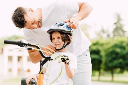 Photo for Selective focus of father putting helmet on son while boy standing near bicycle and looking away - Royalty Free Image