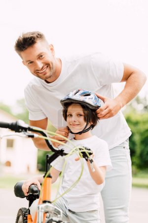 Photo for Selective focus of father and son looking at camera while dad putting helmet on boy - Royalty Free Image