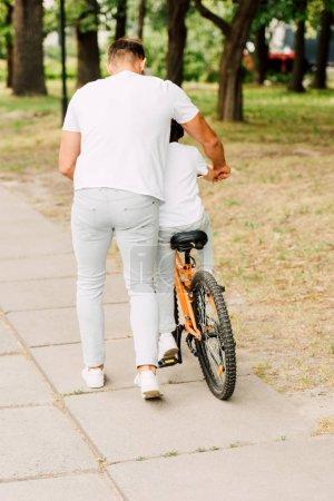 Photo pour Vue pleine longueur du fils conduisant le vélo tandis que le père aidant le garçon - image libre de droit