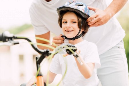 Photo for Selective focus happy son looking at camera while father putting helmet - Royalty Free Image