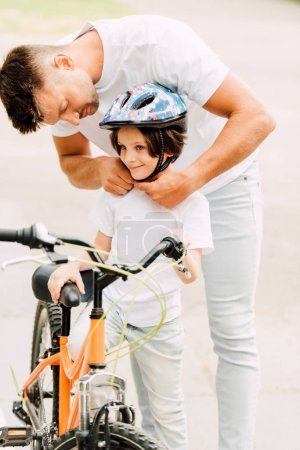 Photo for Father putting helmet on son while boy standing near bicycle and looking away - Royalty Free Image