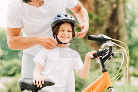 Photo for Cropped view of father putting helmet on son while boy smiling and standing near bicycle - Royalty Free Image