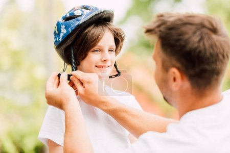 Photo for Selective focus of happy son looking at dad while father putting helmet - Royalty Free Image