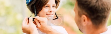 Photo for Panoramic shot of son smiling and looking at dad while father putting helmet - Royalty Free Image