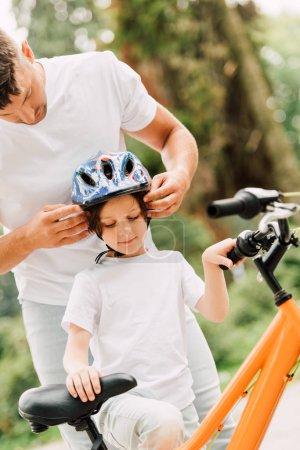 Photo pour Père mettre casque sur fils tandis que garçon essayant de s'asseoir sur le vélo - image libre de droit
