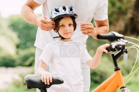 Photo pour Vue recadrée de garçon regardant la caméra tandis que le père mettant casque sur son fils - image libre de droit