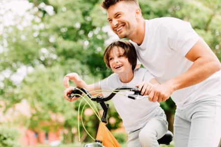 happy father and son looking forward while boy pointing with finger and dad helping kid to ride on bicycle