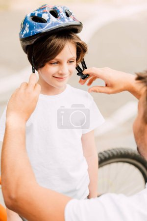 Photo for Selective focus of boy looking at dad and smiling while father putting helmet on kid - Royalty Free Image