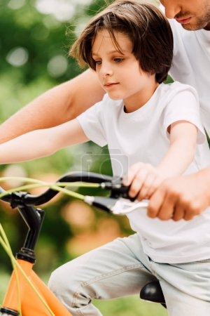 Photo for Cropped view of father holding handles of bicycle while son riding on bike - Royalty Free Image
