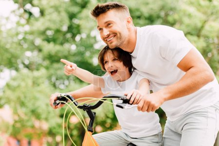 excited father and son looking forward while boy pointing with finger and dad helping kid to ride on bicycle