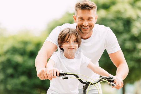 happy father and son looking at camera while boy siting on bicycle dad standing near kid