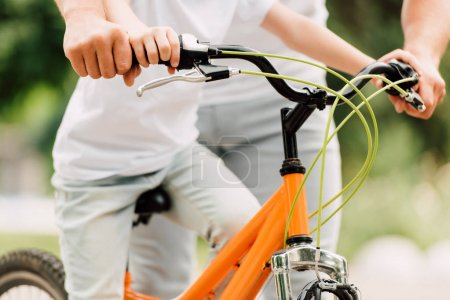 Photo for Cropped view of father and son holding handles of bicycle while kid sitting on bike - Royalty Free Image
