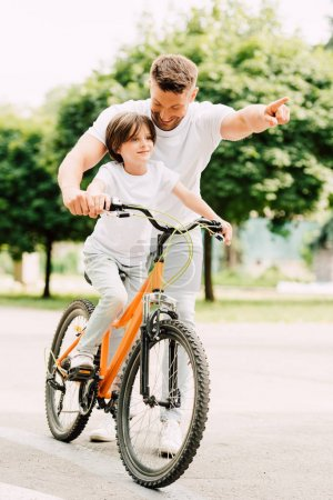 Photo for Full length view of son riding bicycle while father pointing with finger - Royalty Free Image