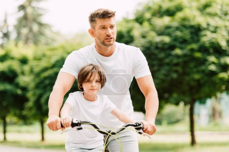 father looking forward while son sitting on bicycle and looking at camera