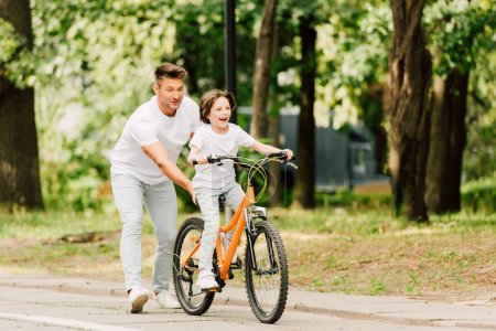Photo for Full length view of father pushing bike while son ridding on bicycle - Royalty Free Image