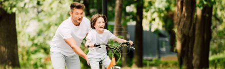panoramic shot of father pushing bike while son riding bicycle
