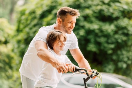 Photo for Selective focus of father and son holding handles of bicycle while looking forward - Royalty Free Image