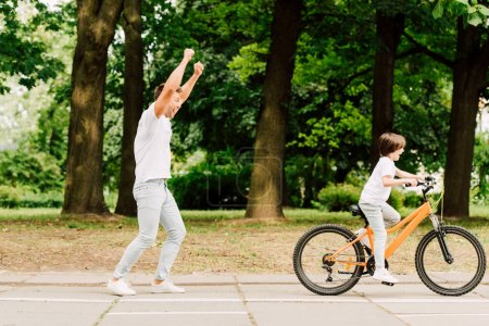 Photo for Full length view of happy father cheering son while kid riding bicycle - Royalty Free Image