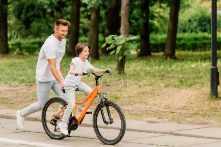 full length view of father pushing sit of bike and running after son while kid riding bicycle