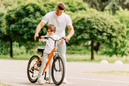 Photo for Full length view of father and son looking on bicycle while standing on road - Royalty Free Image
