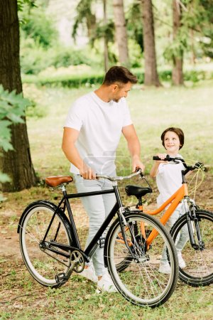 full length view of father and son with bicycles looking at each other
