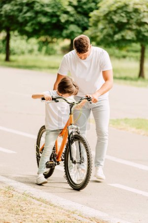 Photo for Full length view of son trying to sit on bicycle while father holding bike - Royalty Free Image