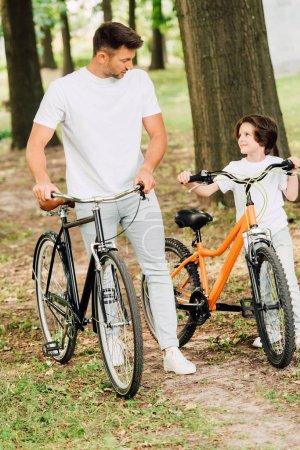 Photo pour Vue pleine longueur du père et du fils marchant dans le parc avec des vélos et se regardant - image libre de droit