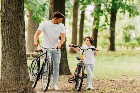 full length view of father and son with bicycles walking in park and looking at each other