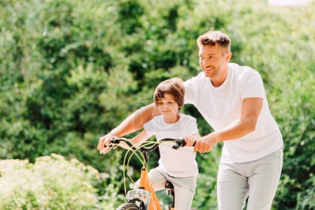 Photo for Father helping son by holding handles of bike while son riding bicycle - Royalty Free Image