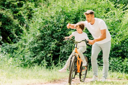 full length view of son riding bicycle while father helping kid and pointing with finger