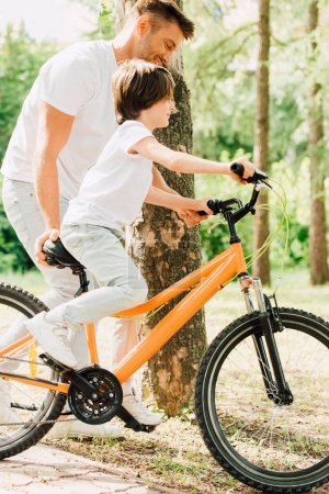 Photo for Side view of son riding bicycle and father walking next to kid and holding sit of bike - Royalty Free Image