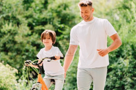 Photo for Son riding bicycle and father walking next to kid and holding sit of bike - Royalty Free Image