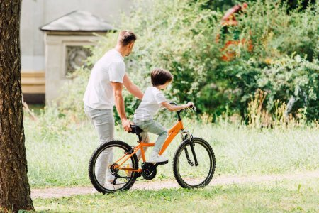 Photo for Full length view of son riding bicycle and father walking next to kid and helping boy to ride on bike - Royalty Free Image