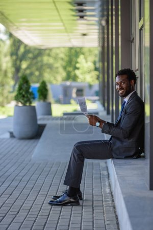 cheerful african american businessman smiling at camera while sitting on parapet and holding newspaper