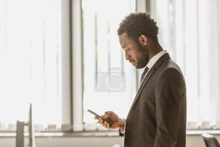 thoughtful african american businessman using smartphone in office