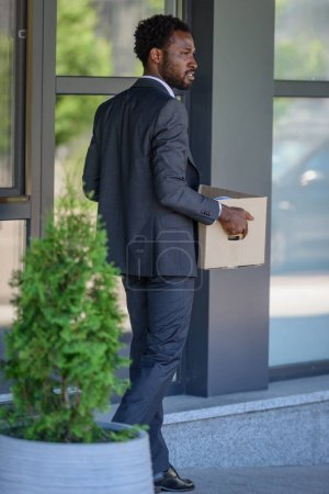 thoughtful african american businessman looking away while carrying carton box
