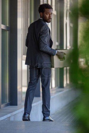 Photo pour Foyer sélectif de l'homme d'affaires afro-américain congédié regardant en arrière tout en retenant la boîte en carton - image libre de droit