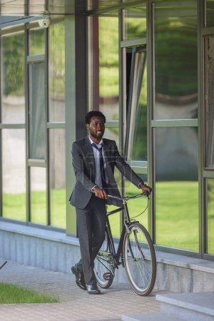 Photo pour Homme d'affaires américain africain de sourire marchant avec le vélo près de l'immeuble de bureaux - image libre de droit