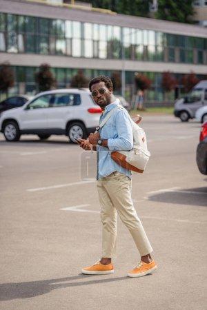 Foto de Guapo hombre afroamericano mirando a la cámara mientras está de pie en el aparcamiento y la celebración de teléfonointeligente - Imagen libre de derechos
