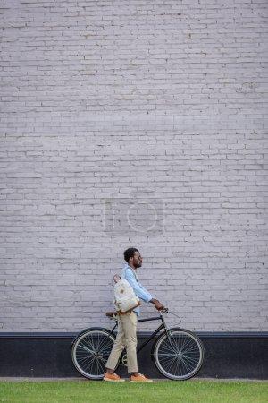 Foto de Elegante hombre afroamericano de pie con la bicicleta cerca de la pared de ladrillo gris - Imagen libre de derechos